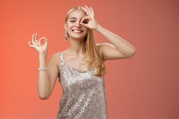 Charmante lustige zarte weibliche blonde freundin tanzen spaß haben perfekte party lächeln breit zeigen okay ok ausgezeichnete geste wie neues kleid grinsen zufriedenstellend, roter hintergrund.
