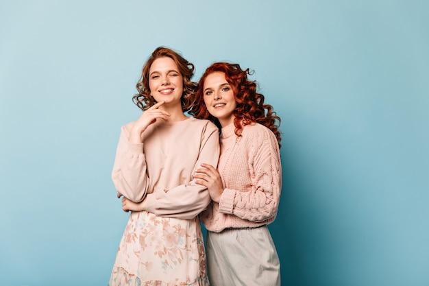 Charmante mädchen, die kamera mit aufrichtigem lächeln betrachten. studioaufnahme der glücklichen freundinnen, die auf blauem hintergrund stehen.