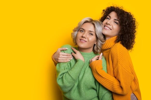 Charmante mädchen mit lockigem haar, die sich auf einer gelben wand mit freiem raum umarmen, während sie nach vorne schauen und lächeln