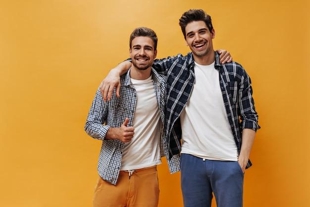 Charmante männer in karierten hemden und weißem t-shirt lächeln an der orangefarbenen wand. cooler bärtiger kerl zeigt friedenszeichen.
