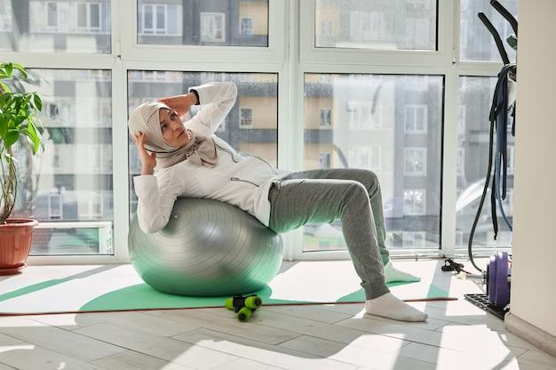 Charmante muslimische frau mit bedecktem kopf im hijab, der bauchmuskeltraining auf einem fitball zu hause-fitnessstudio durchführt