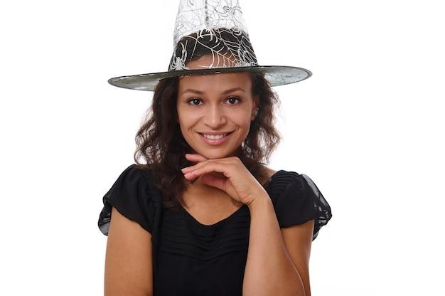 Charmante mysteriöse hispanische brünette mit hexenhut und schwarzem outfit lächelt mit süßem zahnigem lächeln, das die kamera einzeln auf weißem hintergrund mit kopienraum für werbung für halloween betrachtet