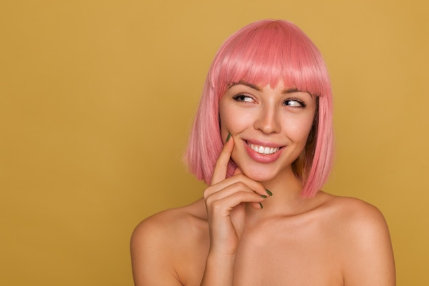 Charmante nachdenkliche junge pinkhaarige frau mit natürlichem make-up, die den zeigefinger auf ihrer wange hält und fröhlich lächelt, während sie über der senfwand steht