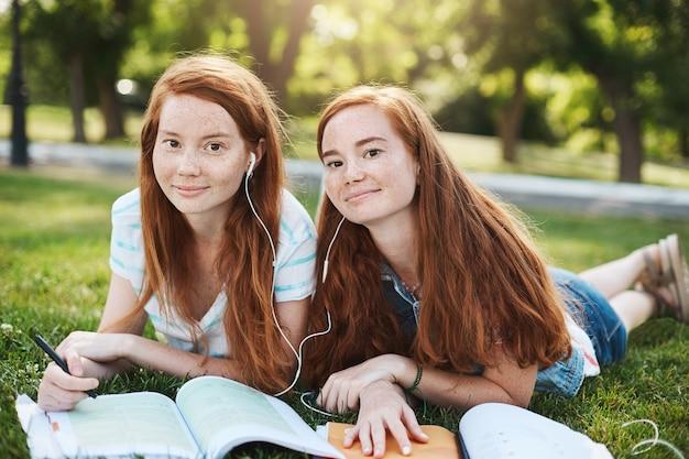 Charmante natürliche rothaarige frauen in sommerkleidung, die am wochenende auf gras liegen, kopfhörer teilen, um gemeinsam lieder zu hören, schwester, die versucht, bei den hausaufgaben zu helfen.