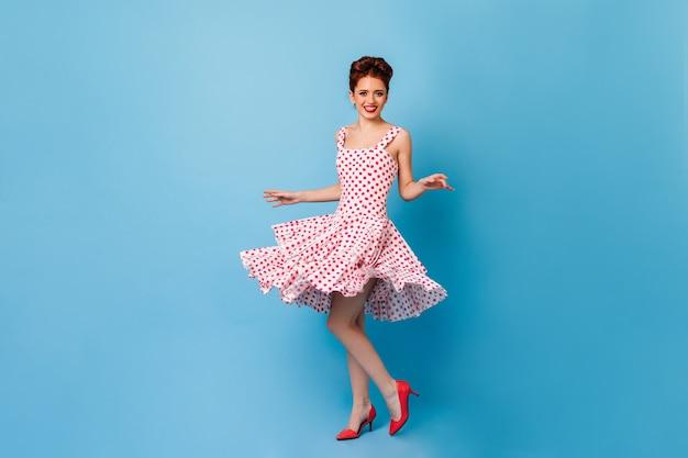 Charmante pinup-frau, die kamera mit aufrichtigem lächeln betrachtet. studioaufnahme des weiblichen modells im gepunkteten kleid, das auf blauem raum tanzt.