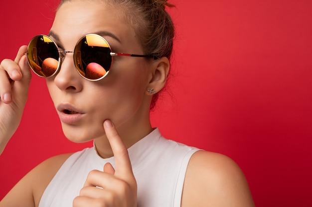Charmante, positiv überraschte junge blonde frau, die über roter hintergrundwand isoliert ist und ein lässiges weißes oberteil und eine stilvolle bunte sonnenbrille trägt, die zur seite schaut.