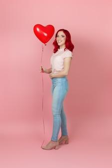 Charmante, positive frau mit roten haaren und jeans hält einen fliegenden roten ballon in der hand