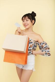 Charmante positive junge frau mit einkaufstüten mit kleidung und schuhen, die sie mit kreditkarte gekauft hat