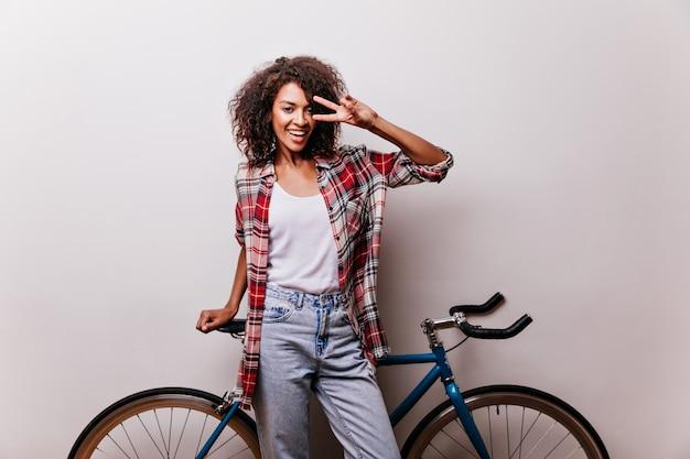 Charmante radfahrerin im karierten hemd lachend. gut gelaunte frau, die mit fahrrad aufwirft und glück ausdrückt.