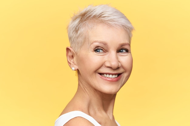 Charmante reife frau mit pixie blondem haar, das mit freudigem lächeln wegschaut, lokalisiert gegen gelben hintergrund mit kopienraum für ihren text aufwirft