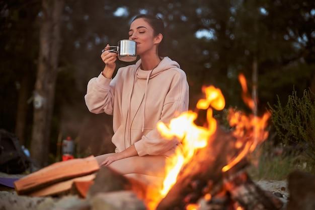 Charmante reisende, die ein heißes getränk genießt, während sie sich in der nähe eines lagerfeuers im wald ausruht?