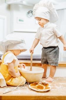 Charmante schmutzige kaukasische kinder kochen teig und pfannkuchen, während sie am wochenende auf einem tisch in der küche sitzen. das konzept der unruhigen kinder von forschern. hausaufgaben für vorschulkinder