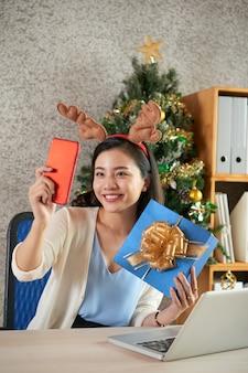 Charmante schöne geschäftsfrau, die mit weihnachtsgeschenk lächelt und fotografiert