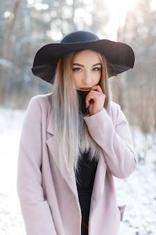 Charmante schöne junge frau mit blonden haaren in einem gestrickten kleid in einem schicken schwarzen hut in einem rosa eleganten mantel, der in einem winterwald aufwirft