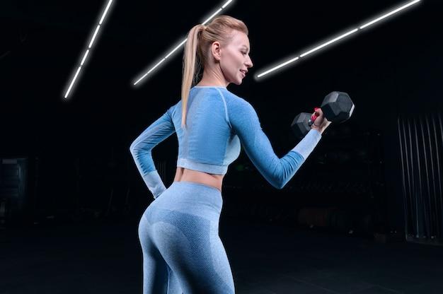 Charmante sportlerin, die in der turnhalle mit hanteln aufwirft. das konzept von bodybuilding, fitness, stretching, gesunder ernährung. gemischte medien
