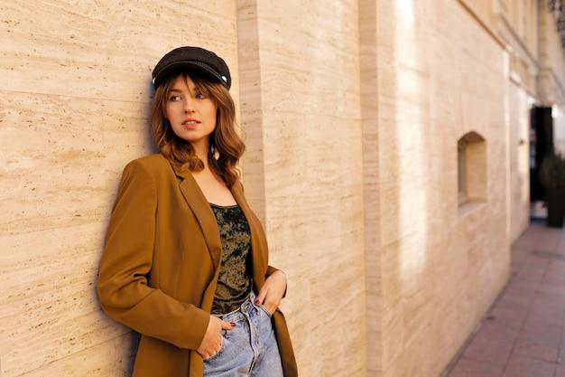 Charmante stilvolle dame in trendiger senfjacke und schwarzer mütze, die draußen im sonnigen warmen tag aufwirft