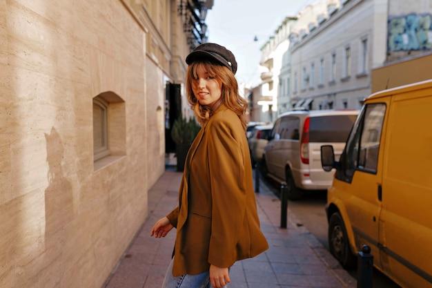 Charmante stilvolle frau mit hellbraunem haar, das schwarze kappe und stilvolle jacke trägt, die die straße entlang in sonnigem tag gehen