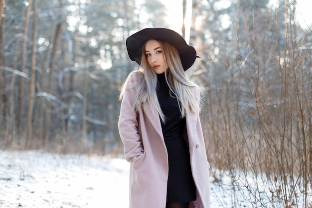 Charmante stilvolle junge frau in einem luxuriösen hut in einem rosa mantel in einem gestrickten golf in einem rock, der im winterwald aufwirft