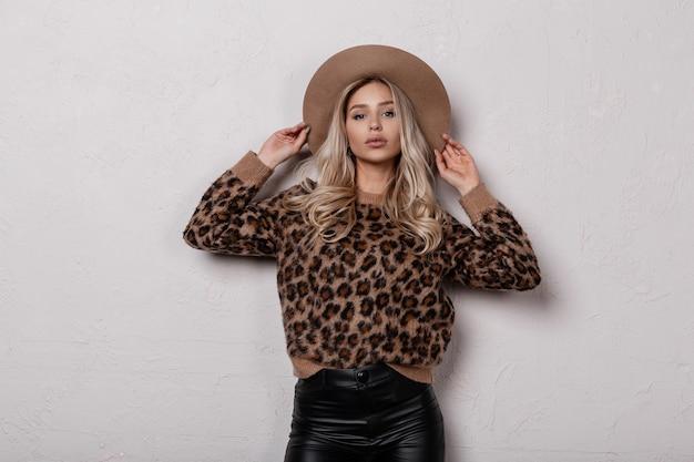 Charmante stilvolle junge frau in einem vintage stilvollen leopardenpullover in schwarzen lederhosen in einem luxuriösen hut, der drinnen nahe einer weißen wand aufwirft