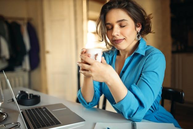 Charmante stilvolle junge texterin, die vor vergnügen die augen schließt, den geruch von kaffee aus der tasse genießt, am laptop arbeitet, einen neuen artikel für social-media-konten schreibt und an ihrem arbeitsplatz sitzt