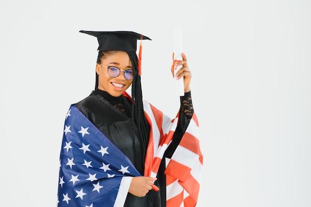 Charmante studentin, die in brillen lächelt, die schwarzen mantel tragen und mit amerikanischer flagge stehen