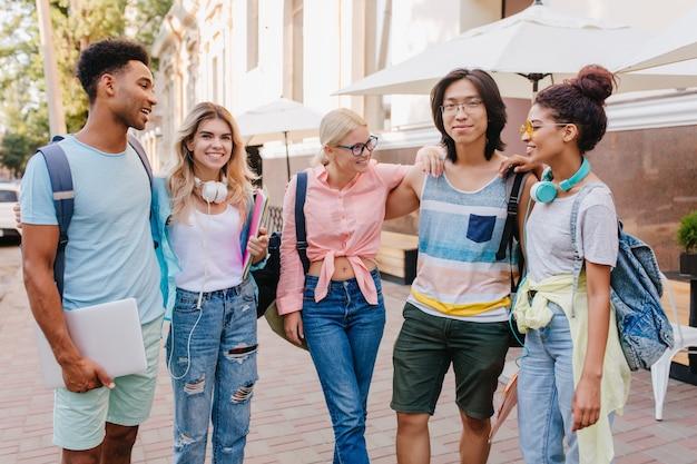 Charmante studentin mit blonden haaren in gläsern, die zwischen klassenkameraden stehen und mit lächeln asiatischen jungen betrachten. glückselige freunde diskutieren prüfungen im freien.