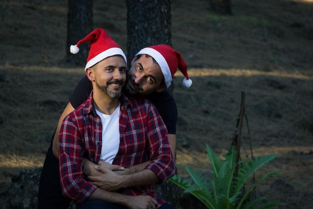 Charmante szene eines jungen homosexuellen paares mit roten weihnachtsmützen im waldpark lächelnde männer umarmen sich