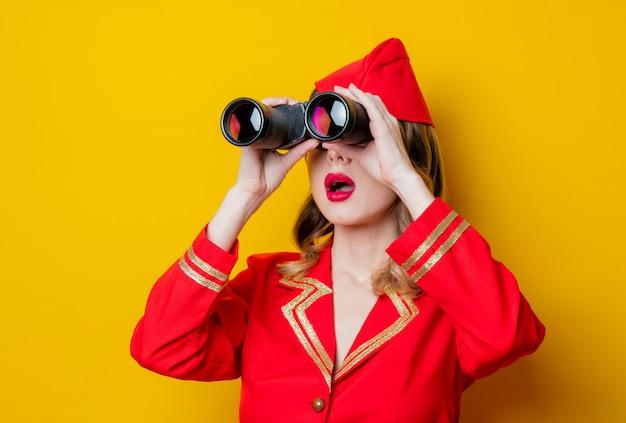 Charmante vintage stewardess in roter uniform mit einem fernglas