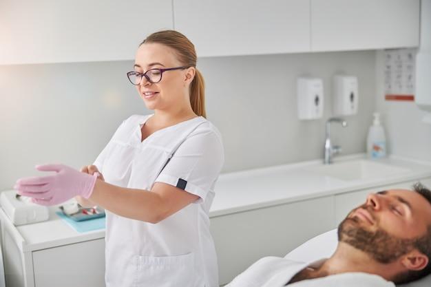 Charmante weibliche kosmetikerin, die rosa handschuh auf ihrer hand betrachtet und lächelt, während sie neben männlichen kunden steht