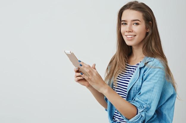 Charmante weibliche moderne junge junge 25er europäische frau langes gesundes haar, das digitale tablette hält sorglos entzücktes lächeln