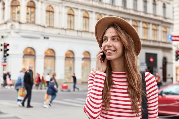 Charmante weibliche reisende geht in städtische umgebung, ruft freund auf modernem smartphone-gerät