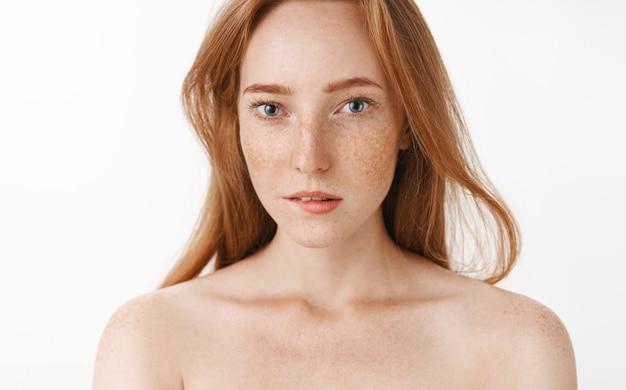 Charmante weibliche rothaarige junge frau mit sommersprossen und schönen blauen augen, die unterlippe von verlangen und interesse beißen und die aufmerksamkeit auf faszinierende sache lenken, die nackt steht