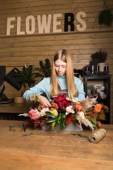 Charmante weibliche verkäuferin, die bunten herbststrauß macht. blumengeschäft und floristisches design meisterklasse-konzept mit kopierraum