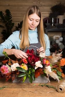 Charmante weibliche verkäuferin, die bunten herbststrauß macht. blumenladen und floristisches meisterklassenkonzept