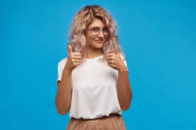 Charmante wunderschöne junge hipsterin mit voluminösen rosa haaren, die glücklich in die kamera lächeln und daumen hoch geste zeigen