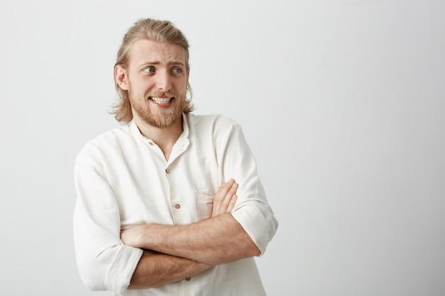 Charmanter blonder mann mit stilvollem haarschnitt, der mit gekreuzten händen steht