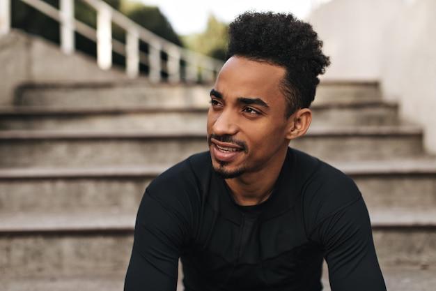 Charmanter brauner lockiger dunkelhäutiger mann im sportlichen langärmeligen schwarzen t-shirt schaut weg, lächelt sanft und posiert in der nähe von treppen