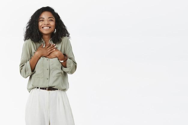 Charmanter charismatischer und entzückter süßer afroamerikaner mit lockigem haar im stilvollen outfit, das dankbar und glücklich fühlt