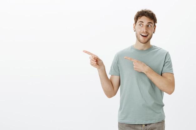 Charmanter emotionaler europäischer mann mit borsten und ohrringen, der mit einem breiten lächeln nach links zeigt und schaut, erstaunt und fasziniert von einem fantastischen gegenstand