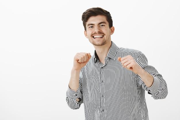 Charmanter erfolgreicher büroleiter, der viel mit speziellem tanz feiert. porträt eines erfreuten fröhlichen europäischen mannes mit schnurrbart, der hände hebt und tanzbewegungen macht, während er mit freunden im club ist
