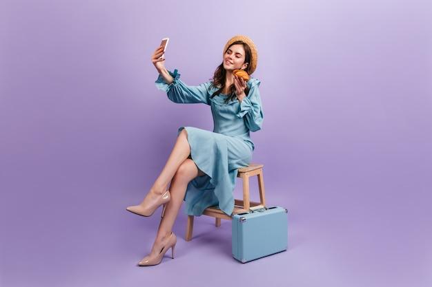 Charmanter französischer reisender, der knuspriges croissant genießt, das auf lila wand sitzt. mädchen im strohhut macht selfie.