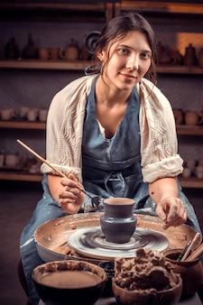 Charmanter handwerkermeister, der an töpferscheibe mit rohem ton mit händen arbeitet. handwerksproduktion.