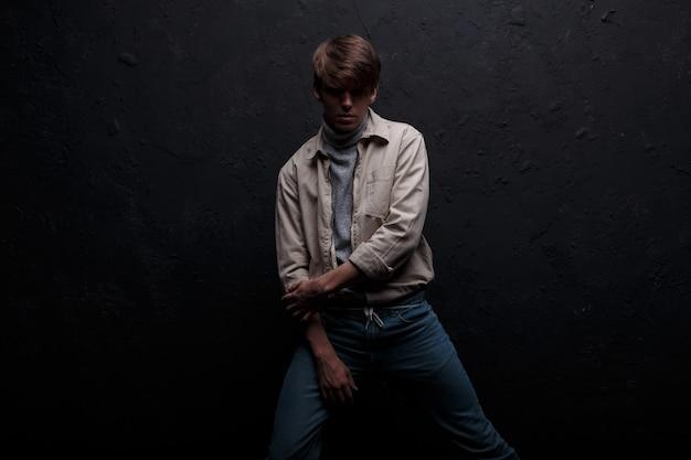 Charmanter hübscher junger mann mit einer modischen frisur in einer frühlingslichtjacke in einem grauen stilvollen golf in modischen blauen jeans posiert für die kamera im studio nahe der grauen wand. männermode.