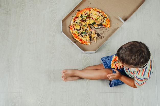 Charmanter junge, der auf dem boden sitzt, der pizza draufsicht isst