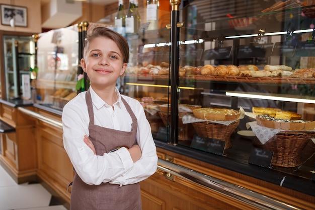 Charmanter junge, der eine schürze trägt und stolz in seiner familienbäckerei posiert