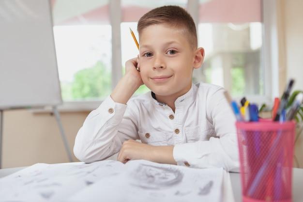 Charmanter junge, der in seinem lehrbuch skizziert