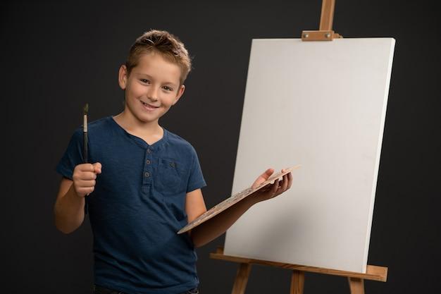Charmanter junge im blauen t-shirt, das kamera betrachtet, die eine palette mit farben hält