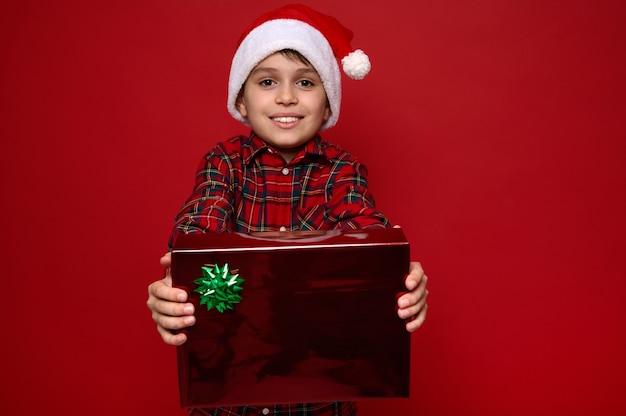 Charmanter junge in weihnachtsmütze und rotem kariertem hemd hält ein weihnachtsgeschenk in rotem glitzerpapier mit glänzendem grünem bogen in seinen ausgestreckten händen und zeigt es der kamera. platz für anzeige kopieren