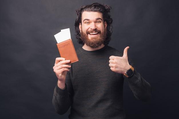 Charmanter junger bärtiger mann im lässigen halten von passkarten und zeigt daumen hoch