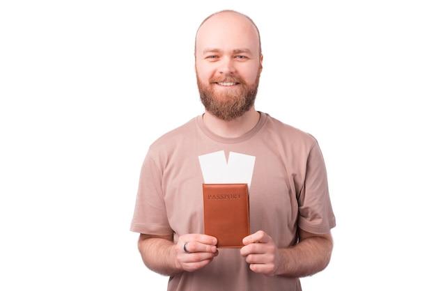 Charmanter junger mann mit bart, der pass und tickets zeigt